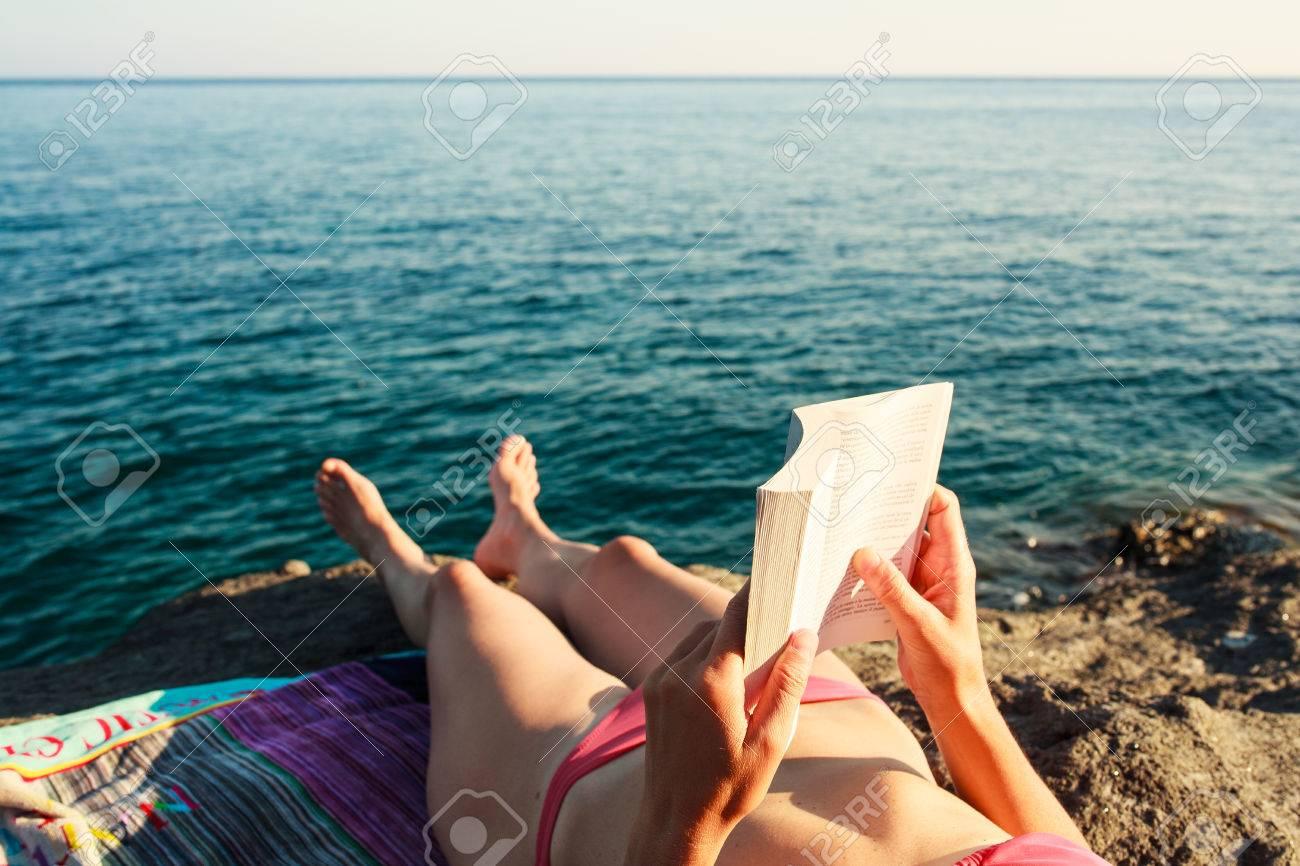 Girl Reading book in the beach, Pantelleria Stock Photo - 22485784