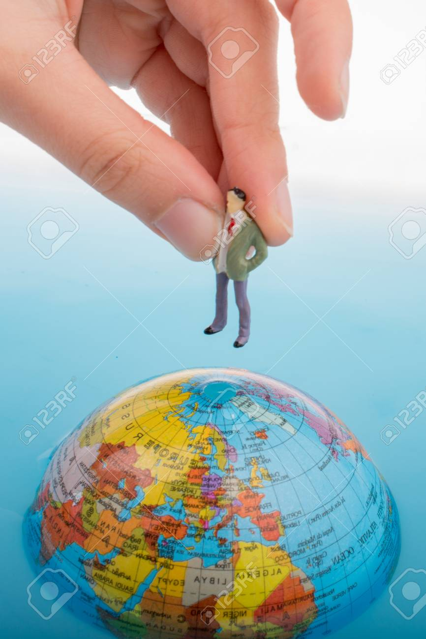 5a179321f566 Hand holding a little figurine on the top of the globe in water Stock Photo  -