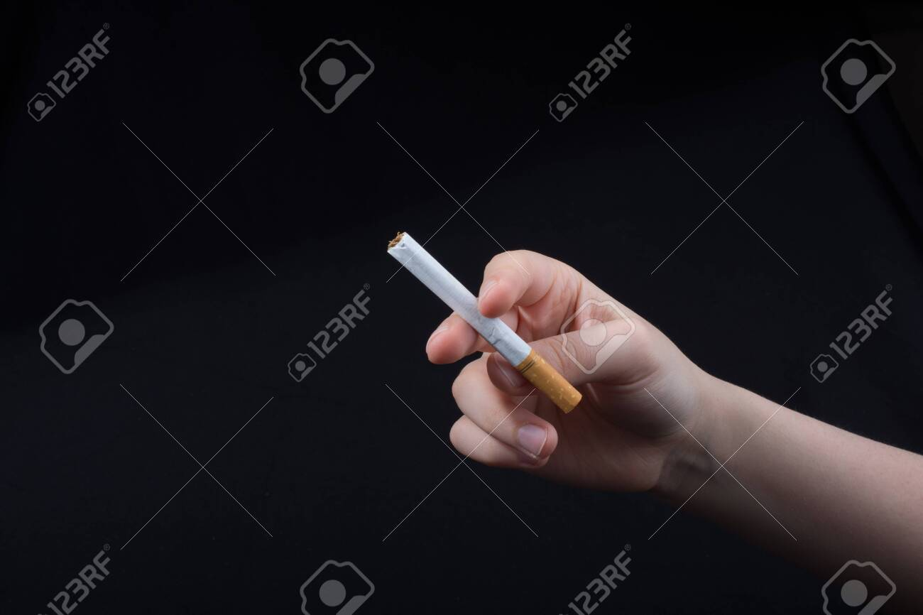 Hand is holding a cigarette on black background - 121493691