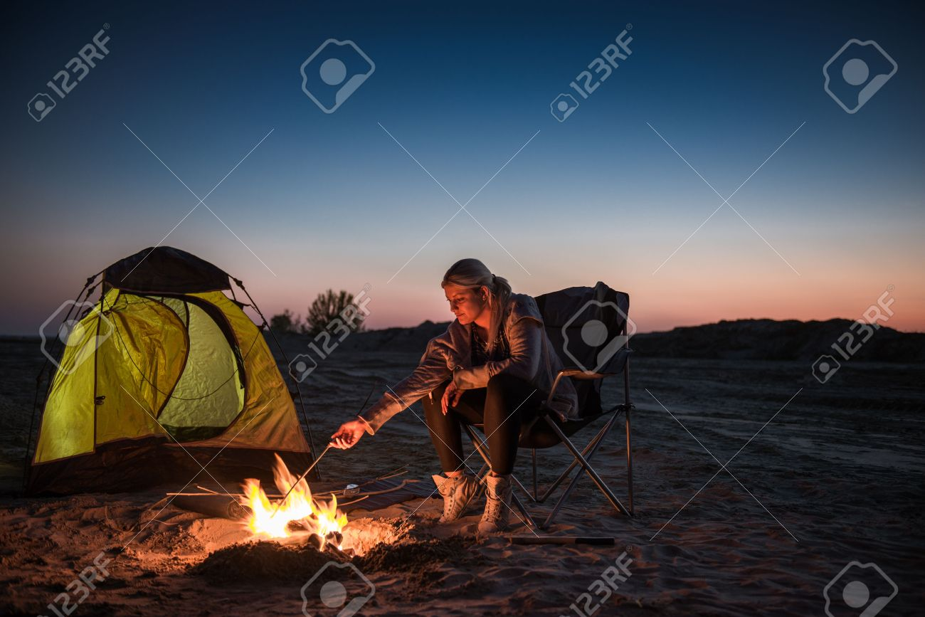 Young girl lighting a fire in front of the tent and a sky full of stars & Young Girl Lighting A Fire In Front Of The Tent And A Sky Full ...