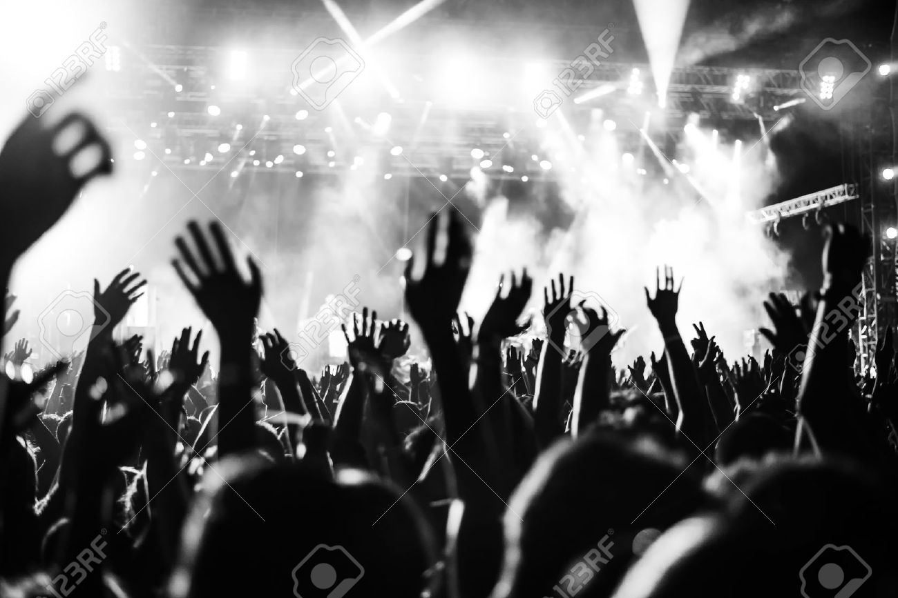 Black and white photo of audience with hands raised at a music festival and lights streaming