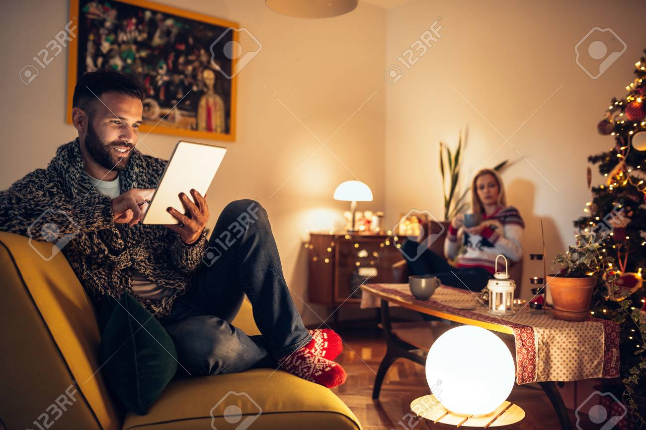 Man enjoying winter holidays at home with his wife. - 66416227