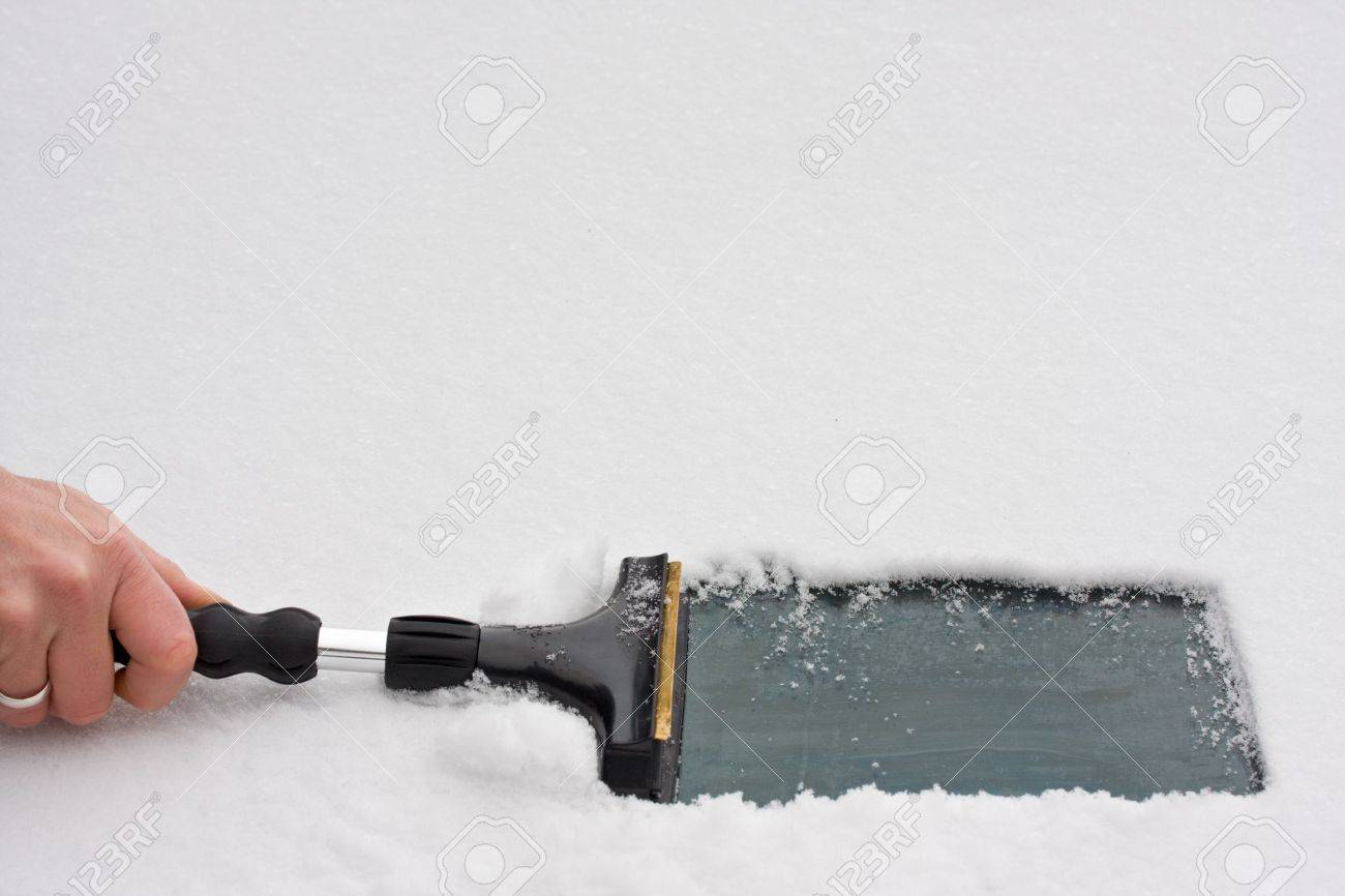 hand with an ice scraper cleaning a windshield Stock Photo - 4121078