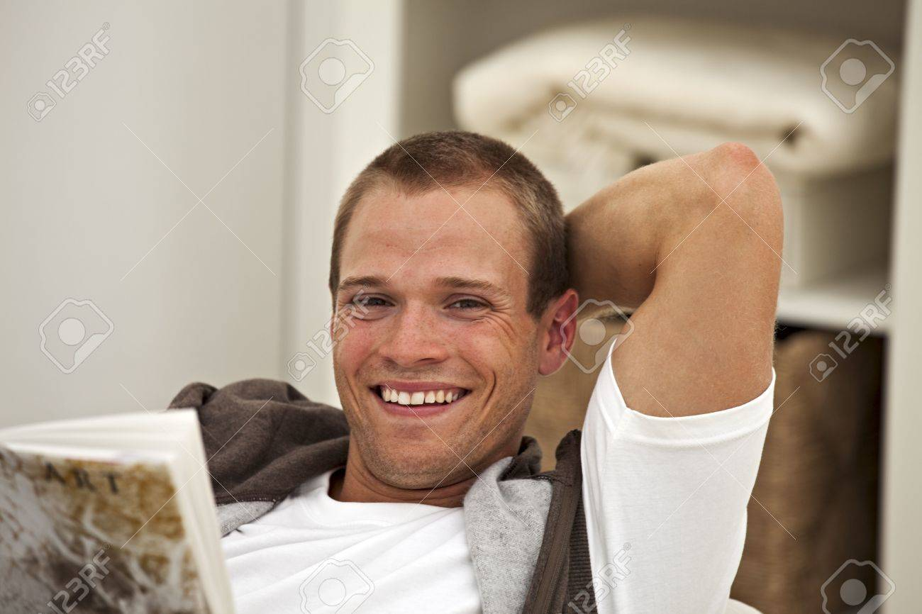 smiling young man reading a book Stock Photo - 5444245