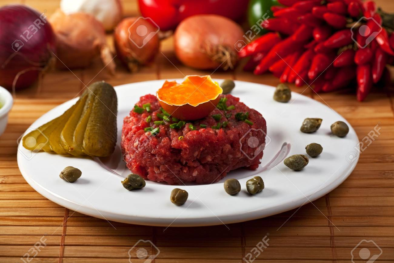 steak tartar with an onion ring and an open egg Stock Photo - 6329779
