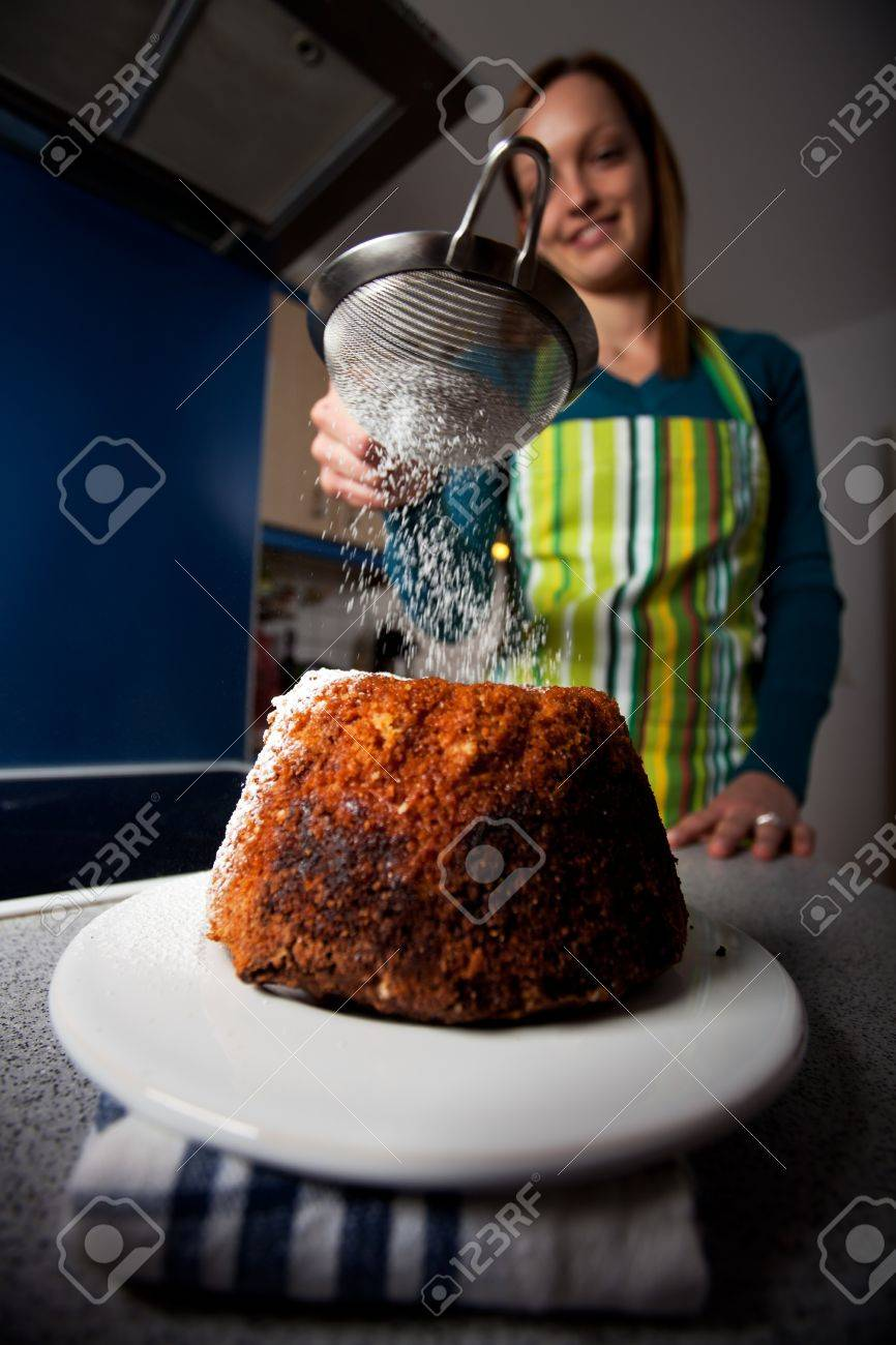 young cheffe dusting sugar on a cake - 8914182