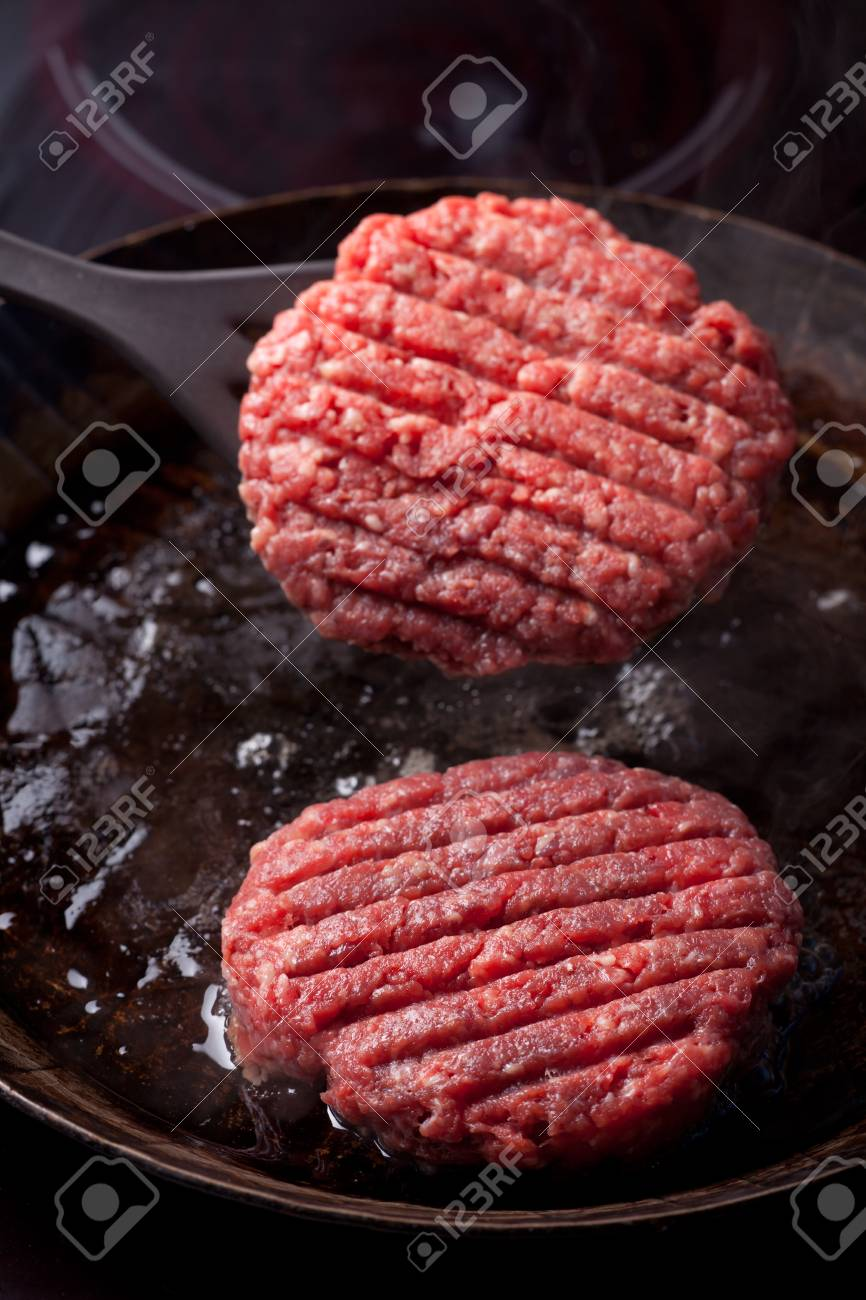 two beef patties in an iron pan Stock Photo - 11960911