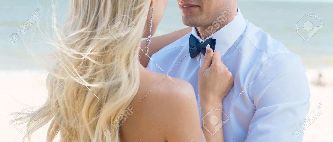 Man groom in wedding suit with bow tie  Hands bride, care, fix,