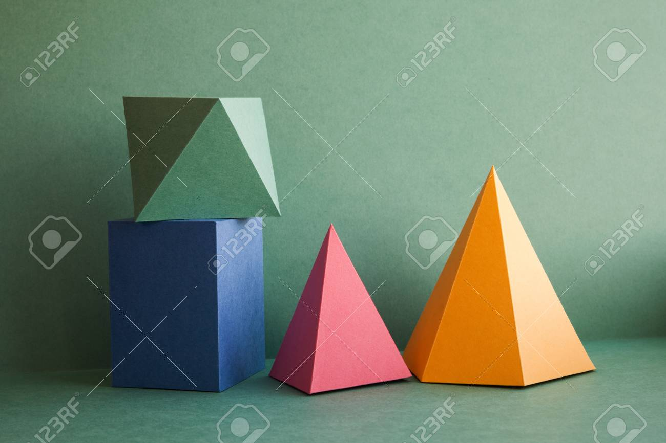 Abstract geometrical solid figures still life. Colorful three-dimensional pyramid prism rectangular cube arranged on green background. Yellow blue pink malachite colored objects textured paper surface. - 75317381