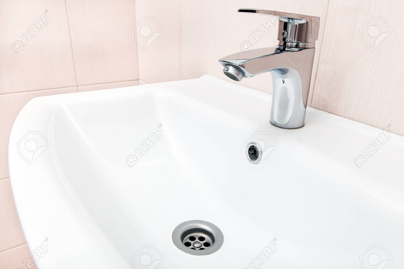 Chrome Faucet In The Ceramic Wash Basin In The Bathroom With.. Stock ...