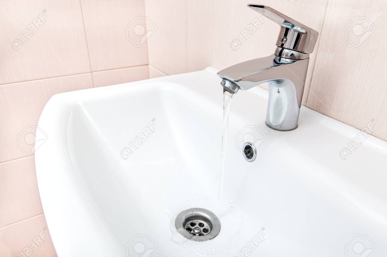 Open Chrome Faucet Water Flow In The Ceramic Wash Basin In The ...