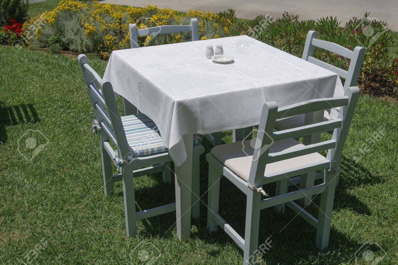 Greek Empty Outdoor Taverna Restaurant Chairs And Table. A Greek  Traditional Tavern With White Tablecloth
