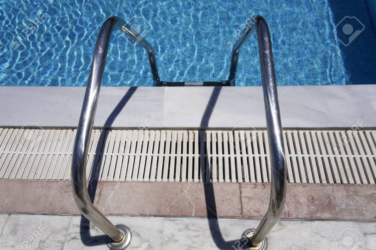 Outdoor Swimming Pool Ladder. Grab Bars Metal Ladder To A Blue ...