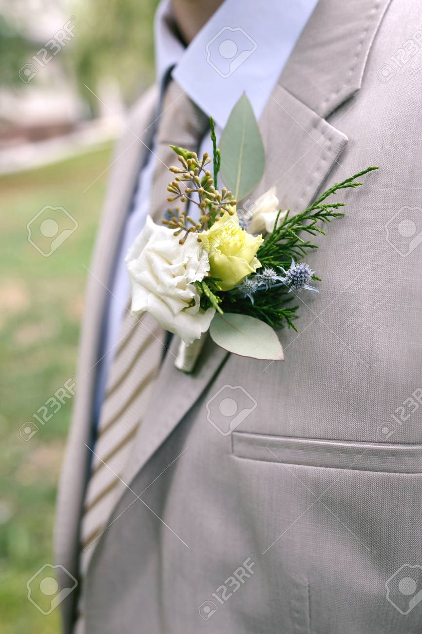 Boutonniere Of White And Yellow Flowers With Greens On Lapel Stock