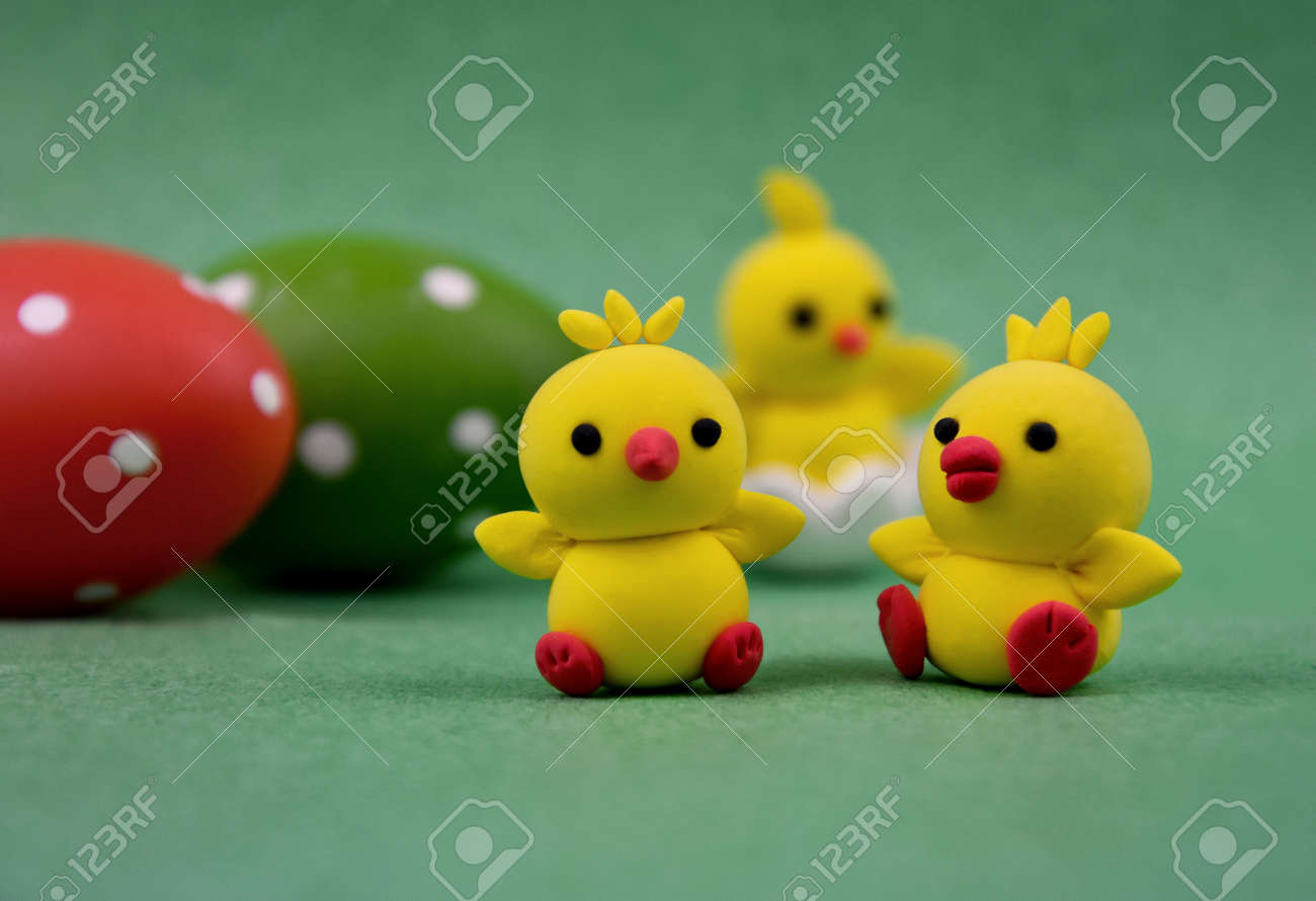 Cute easter baby chicks toys on a green background stock images. Little yellow chickens easter decoration on a green background. Easter adorable chickens and eggs stock photo - 166006318