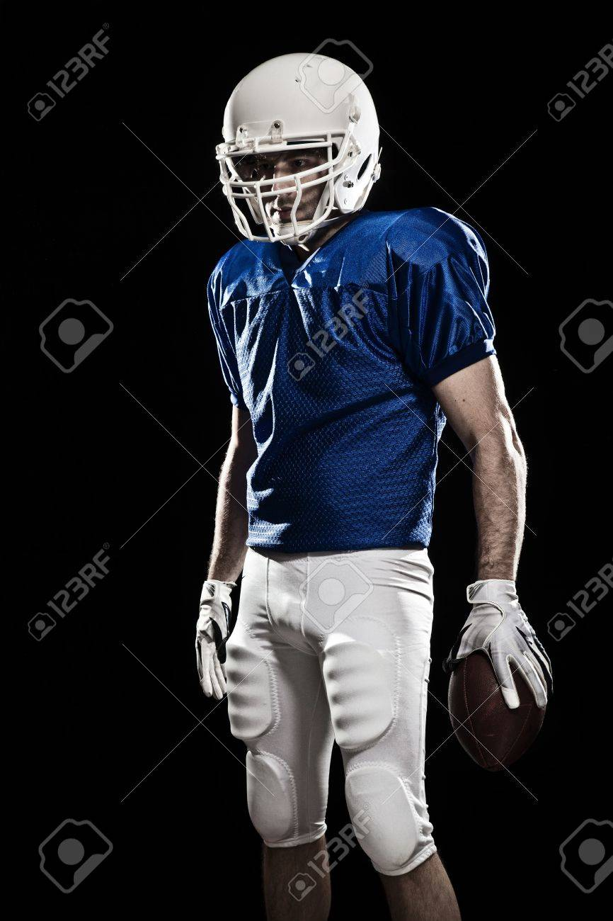 Football Player with number on a blue uniform and a ball in the hand. Studio shot. - 19900672