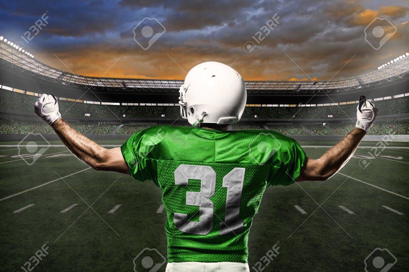 Football Player with a green uniform celebrating with the fans. - 21782159