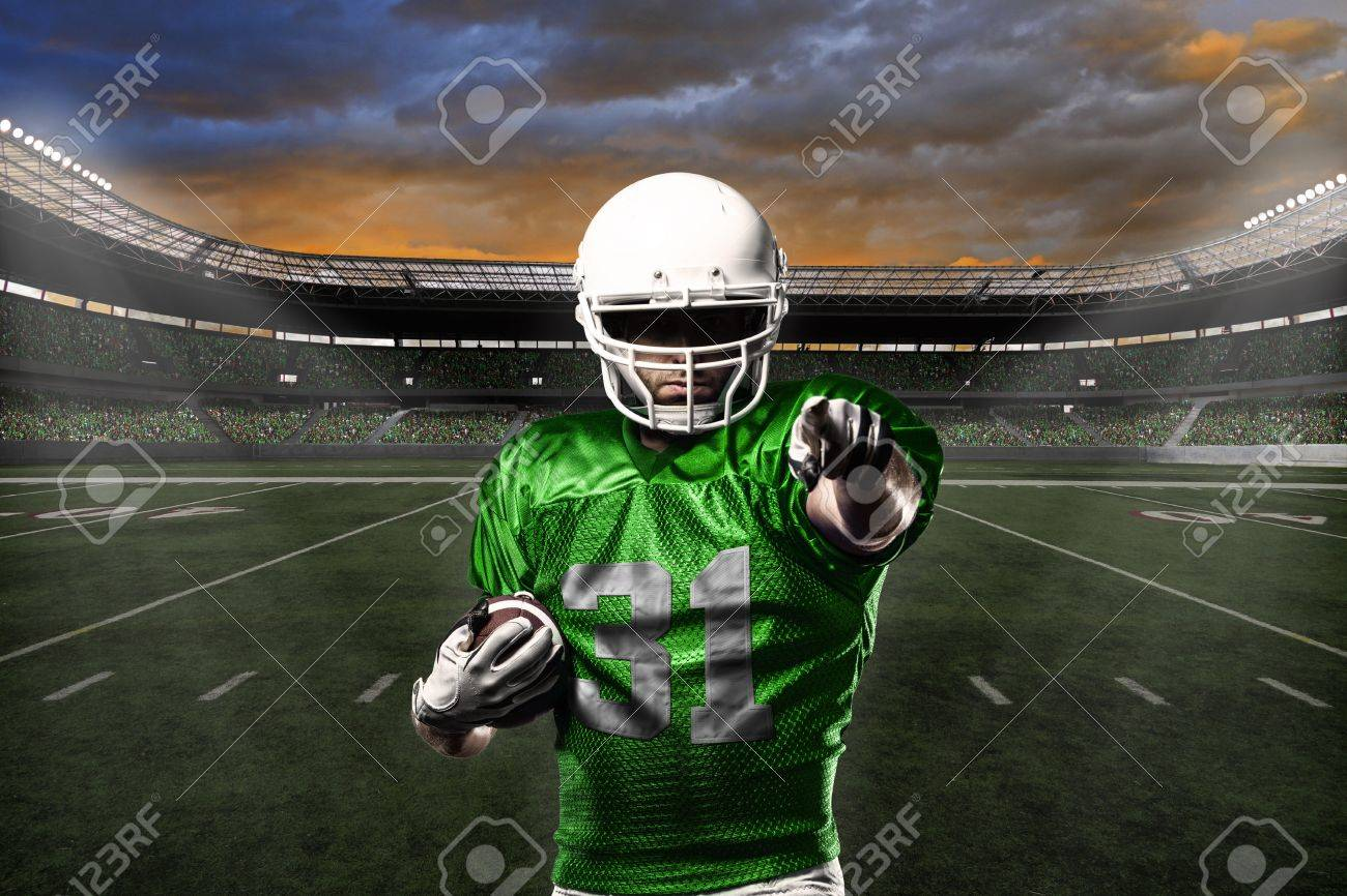 Football Player with a green uniform celebrating with the fans. - 21782203