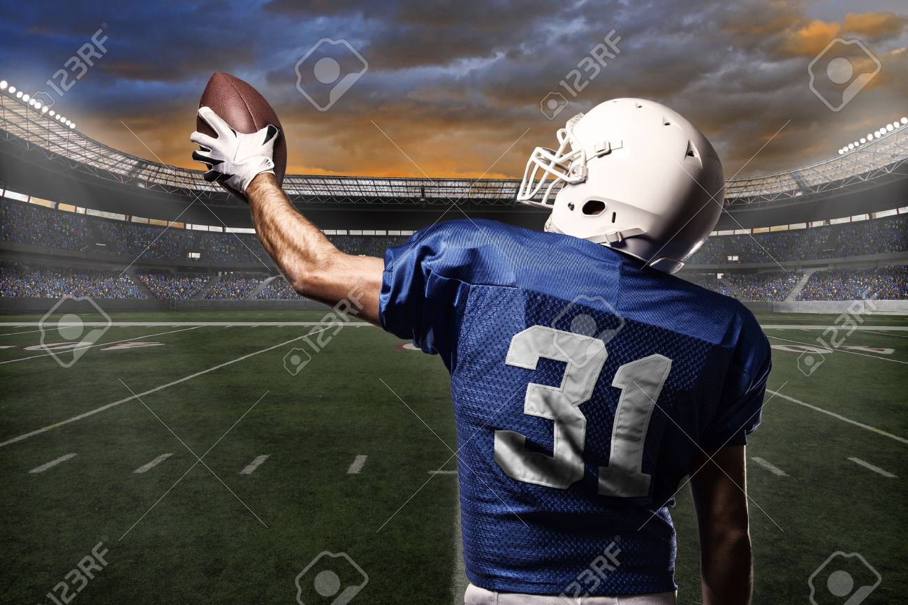 Football Player with a blue uniform celebrating with the fans. - 21782202