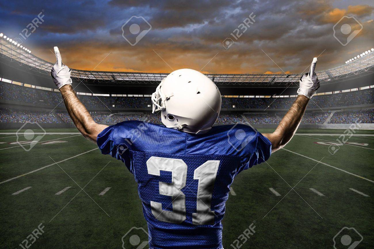 Football Player with a blue uniform celebrating with the fans. - 21782208