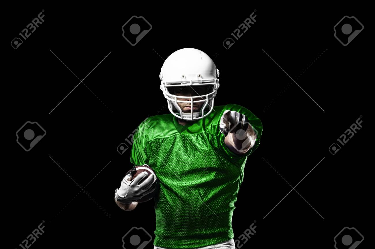 Football Player with a Green uniform celebrating on a black background. - 24352290