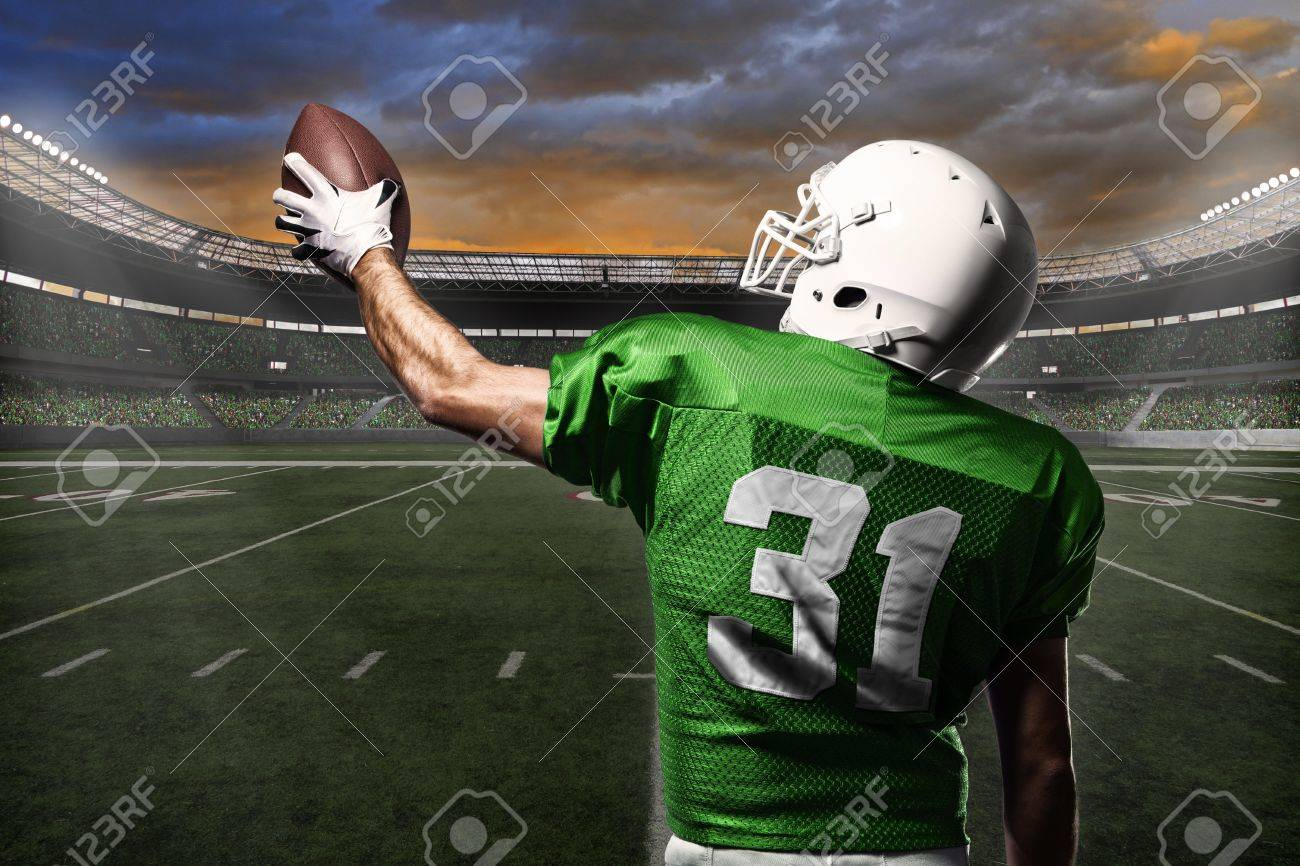 Football Player with a green uniform celebrating with the fans. - 21782326