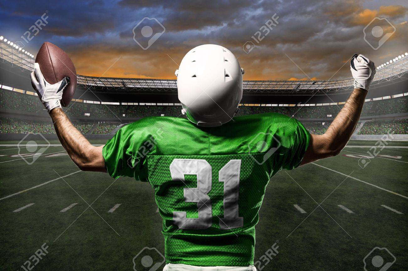 Football Player with a green uniform celebrating with the fans. - 21782327