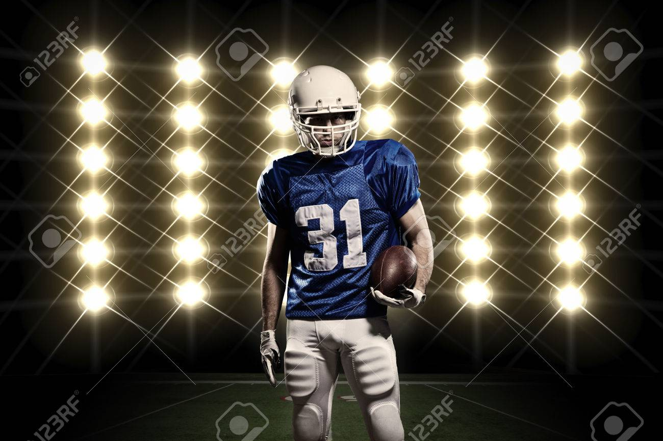 Football Player with a Blue uniform in front of lights - 24359923