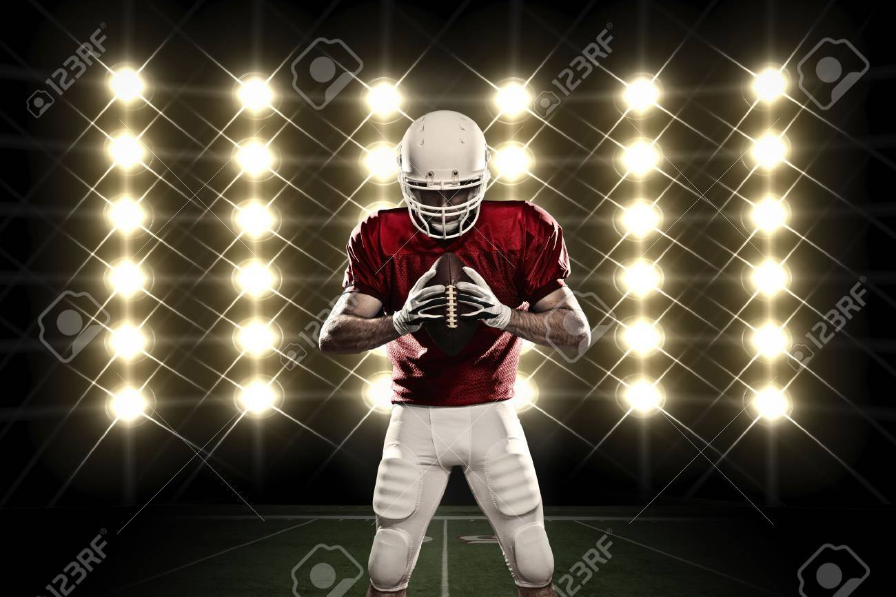 Football Player with a Red uniform in front of lights. - 24359929