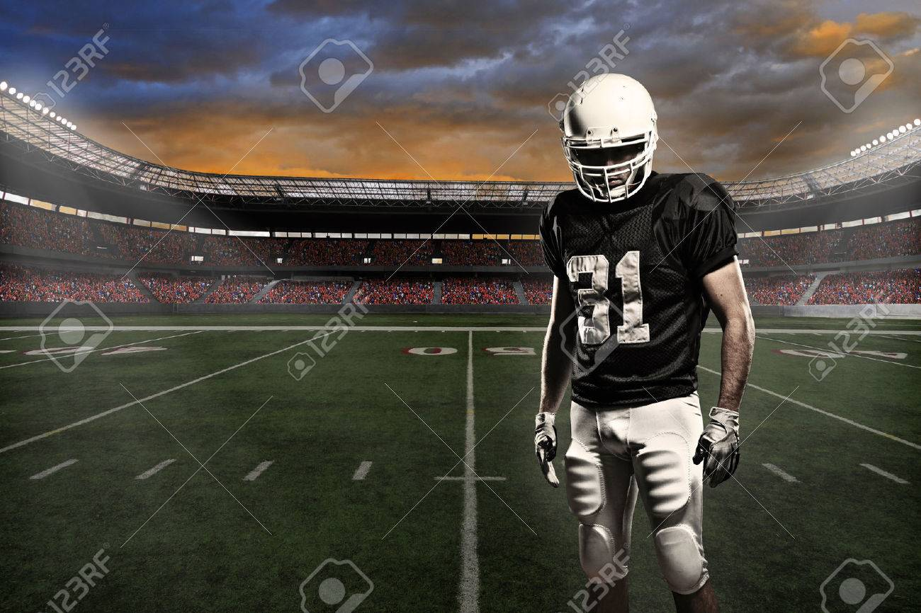 Football player with a black uniform, in a stadium. - 24750184