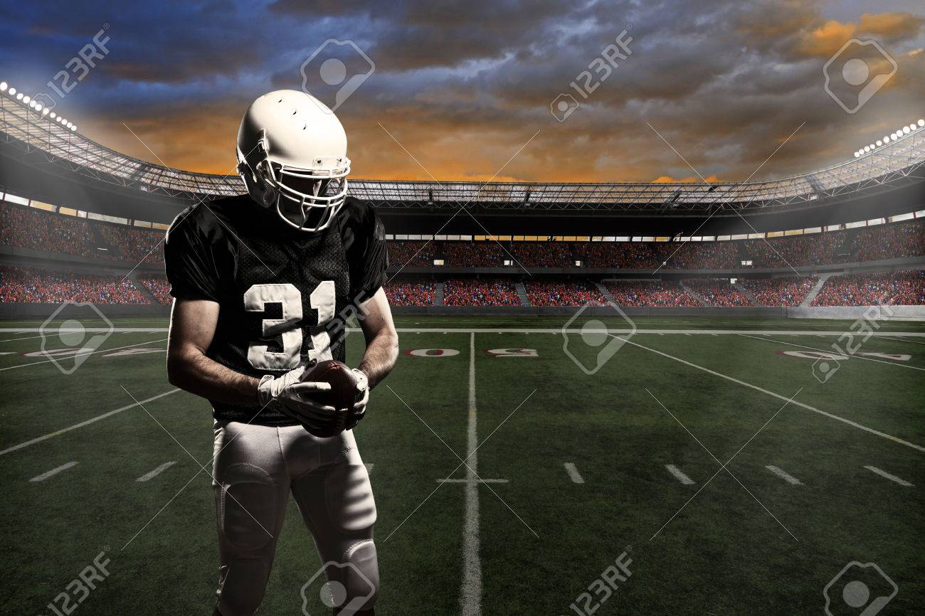 Football player with a black uniform, in a stadium. - 24750186