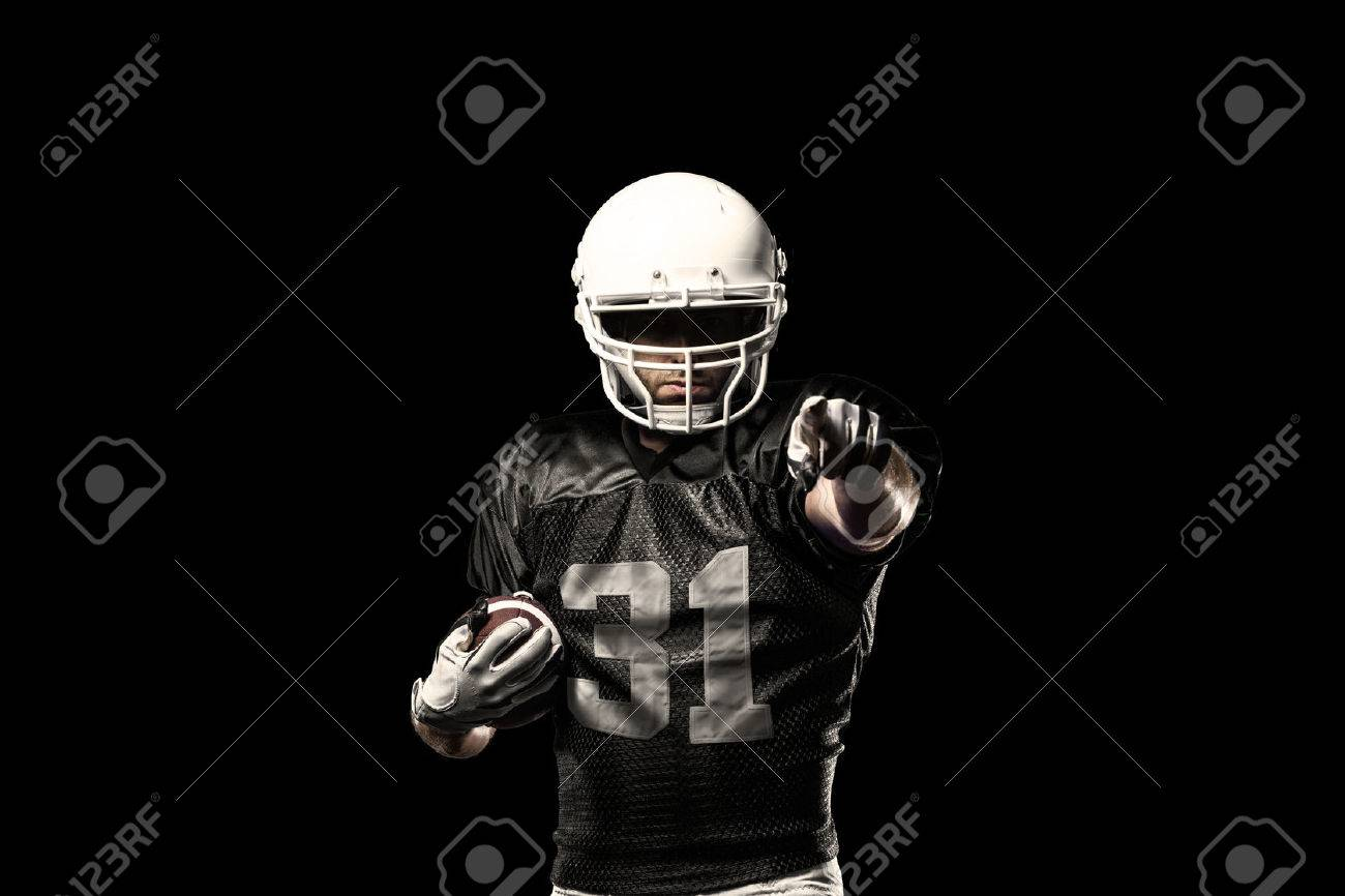 Football Player with a black uniform, on a black background. - 24750219