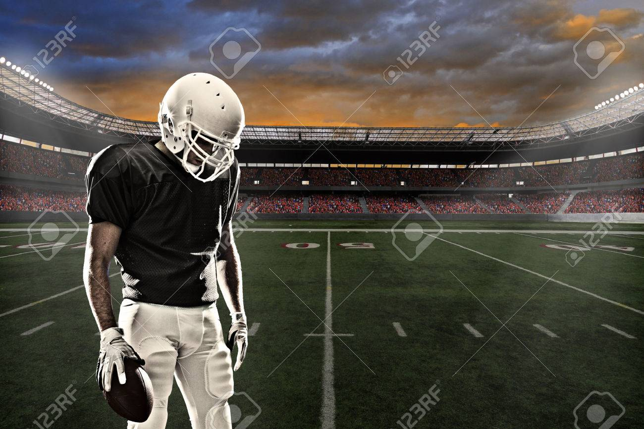 Football player with a black uniform, in a stadium. - 24750221