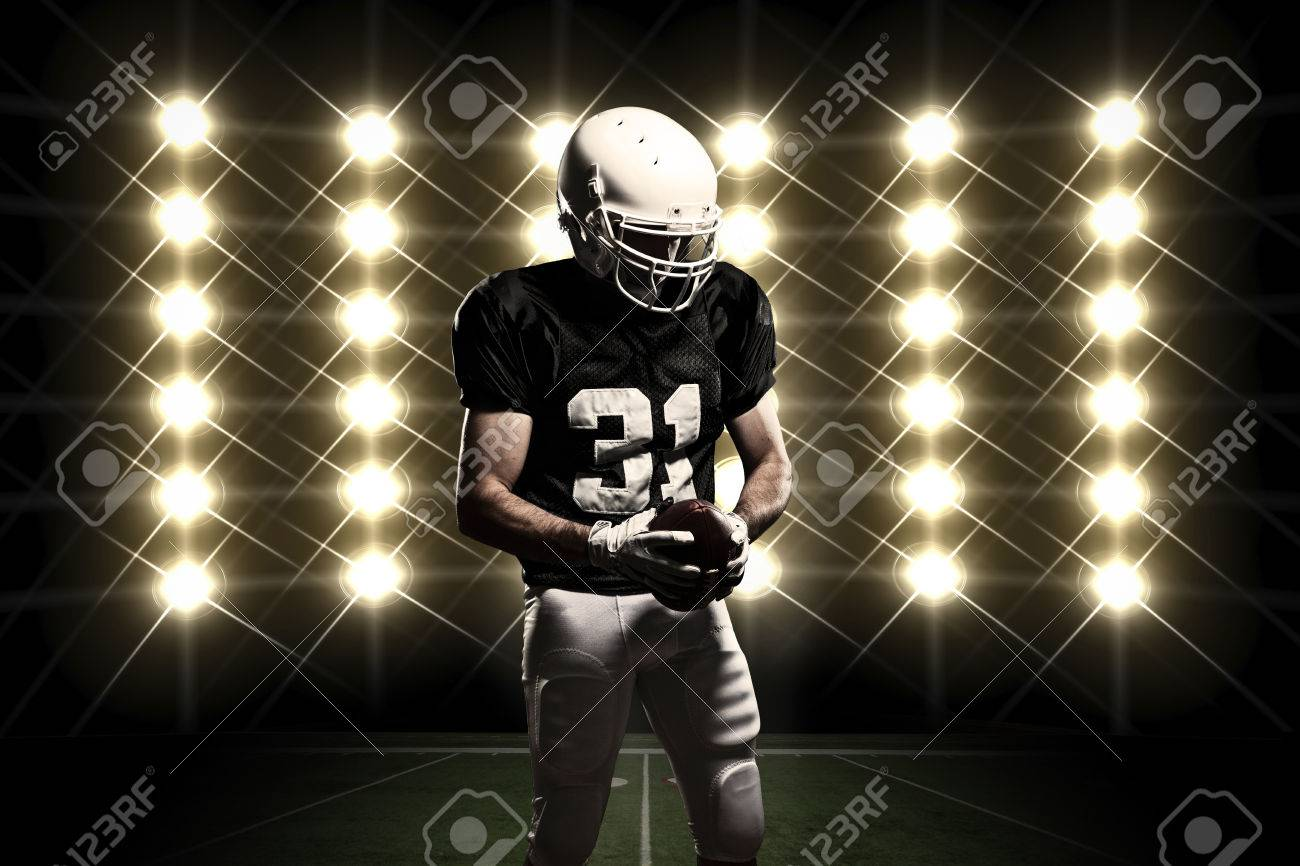 Football Player with a black uniform celebrating in front of lights. - 24750236