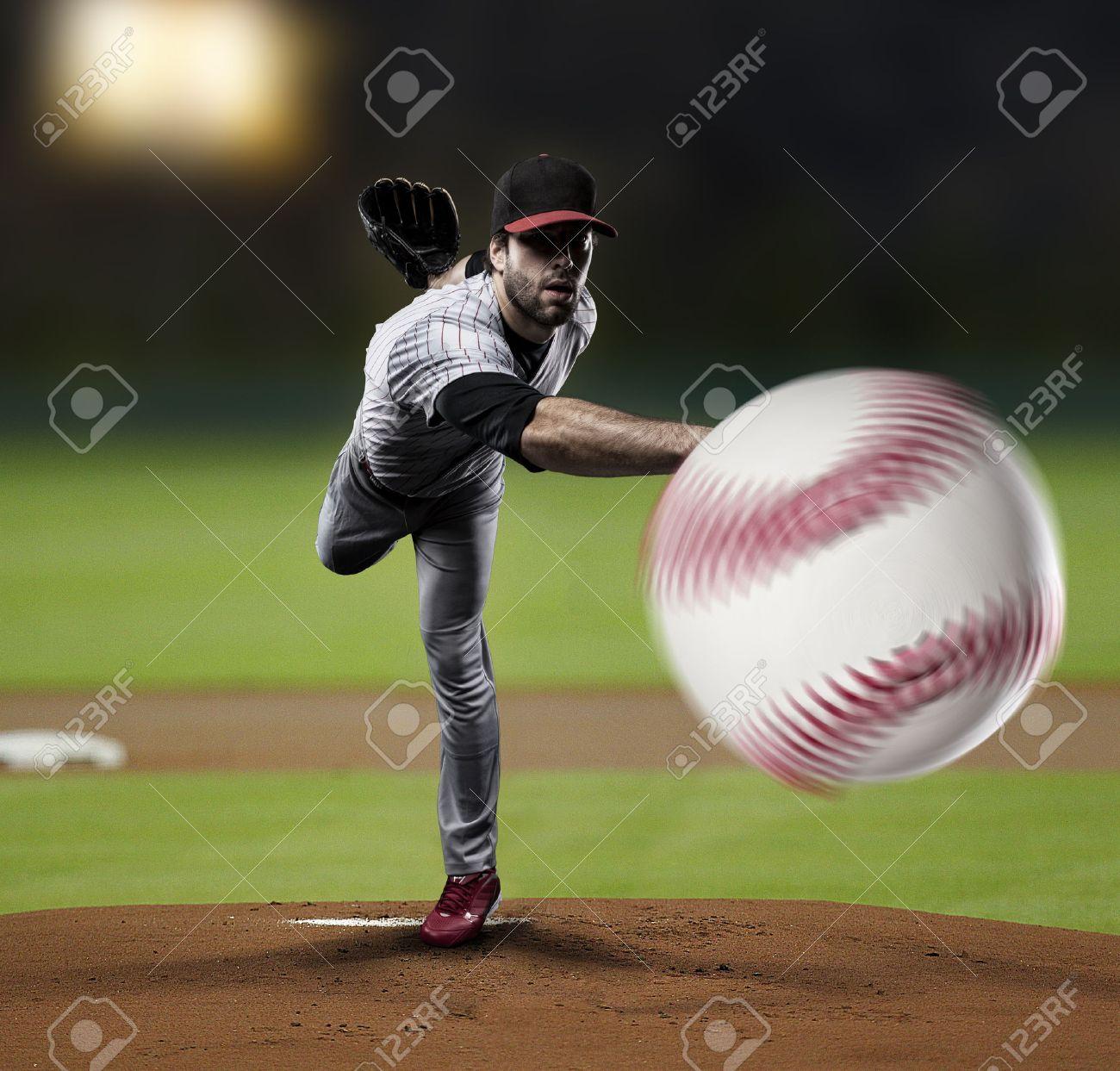 Pitcher Player throwing a ball, on a baseball Stadium. - 27529280