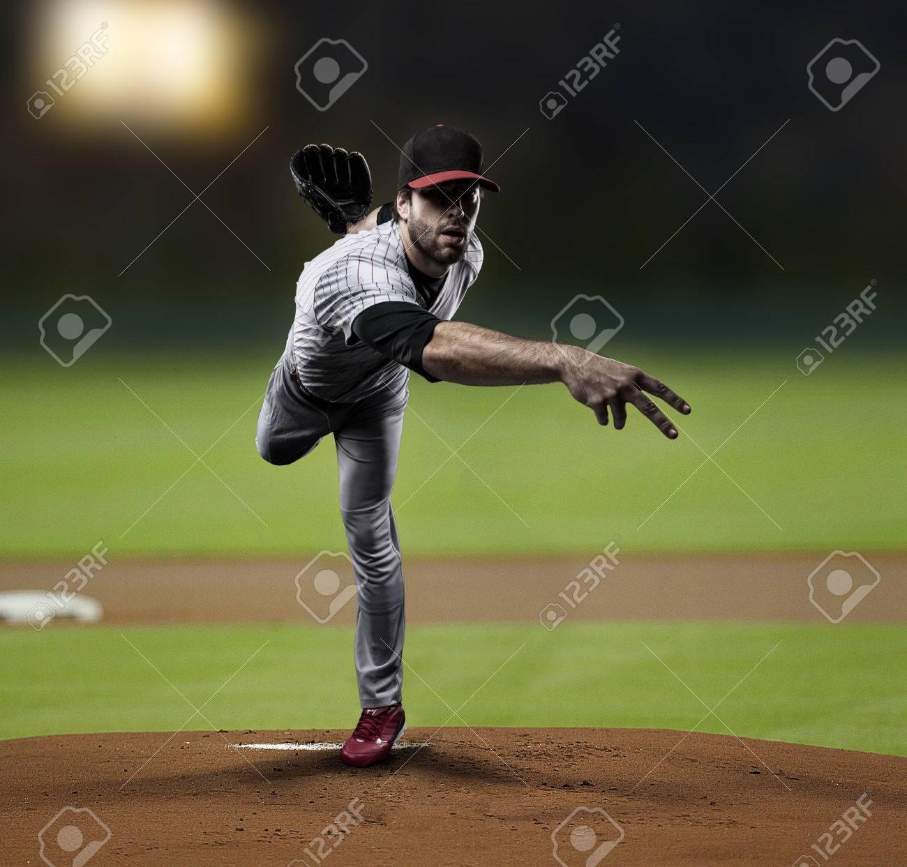 Pitcher Player throwing a ball, on a baseball Stadium. - 27529281