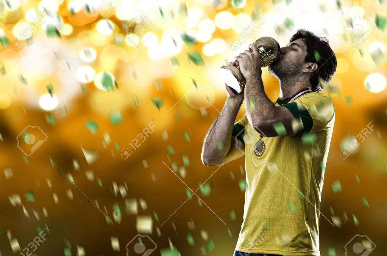 Brazilian soccer player, celebrating the championship with a trophy in his hand, on a yellow background. - 28208627