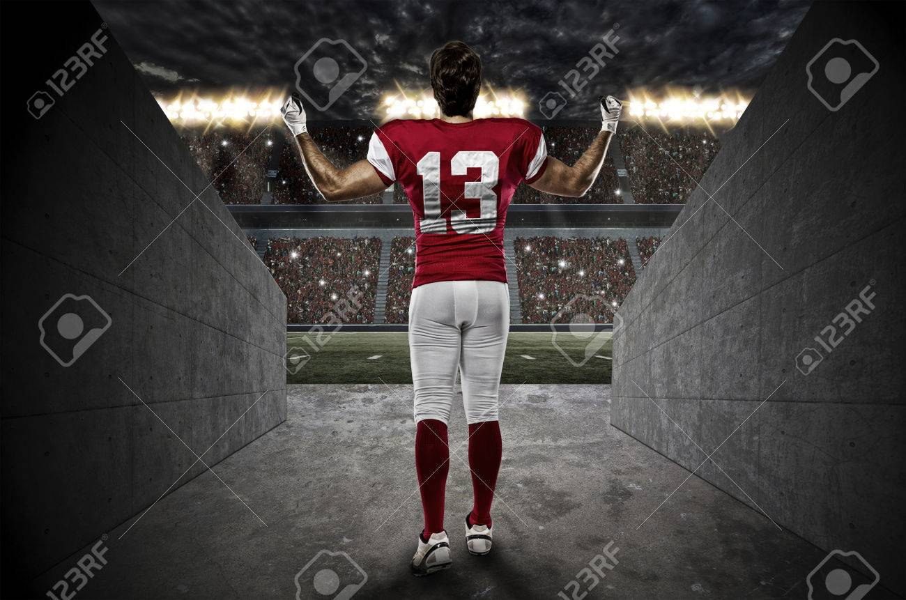 Football Player with a red uniform walking out of a Stadium tunnel. - 35218291