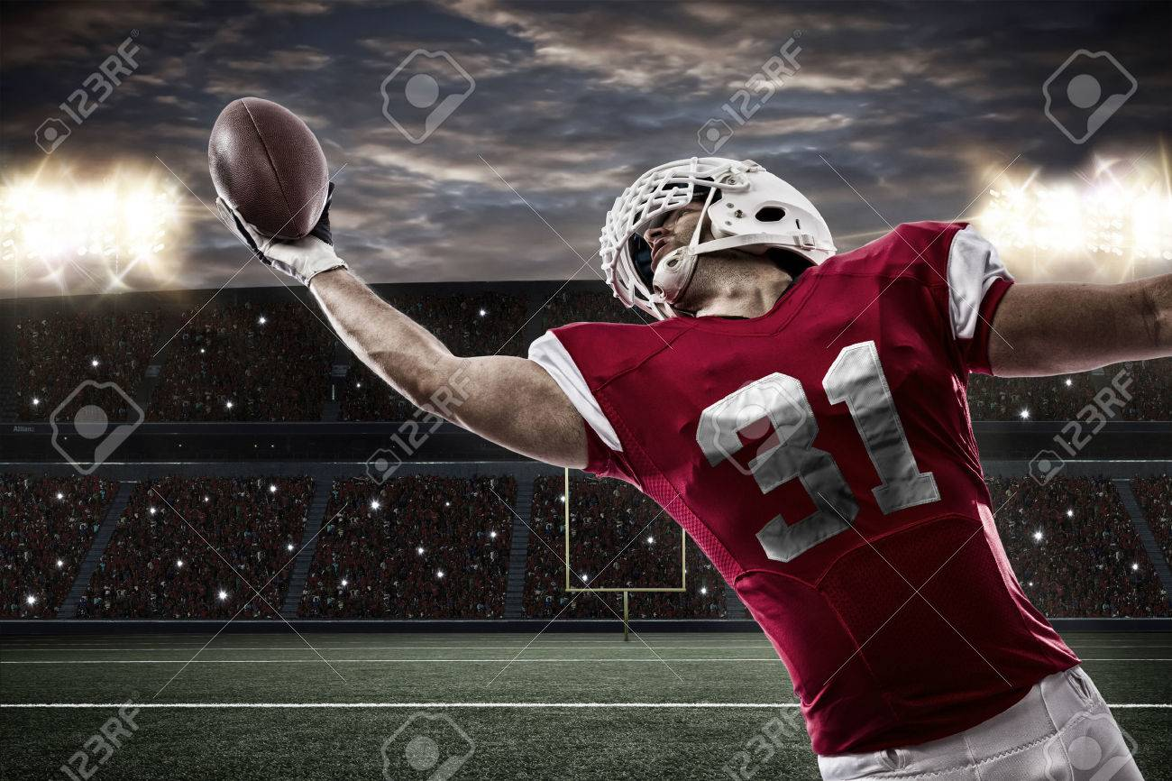Football Player with a red uniform catching a ball on a stadium.. - 35218342