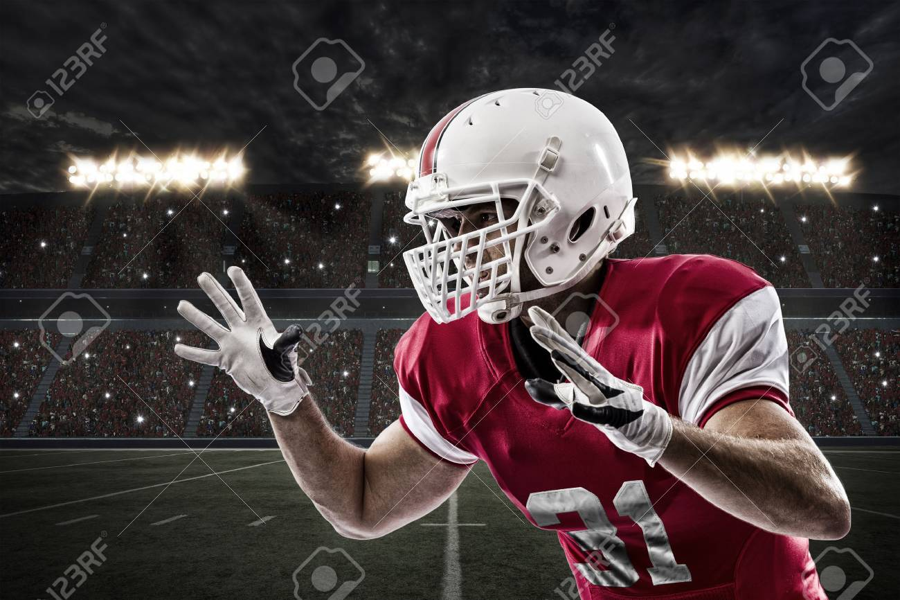 Football Player with a red uniform making a tackle on a Stadium. - 35219261