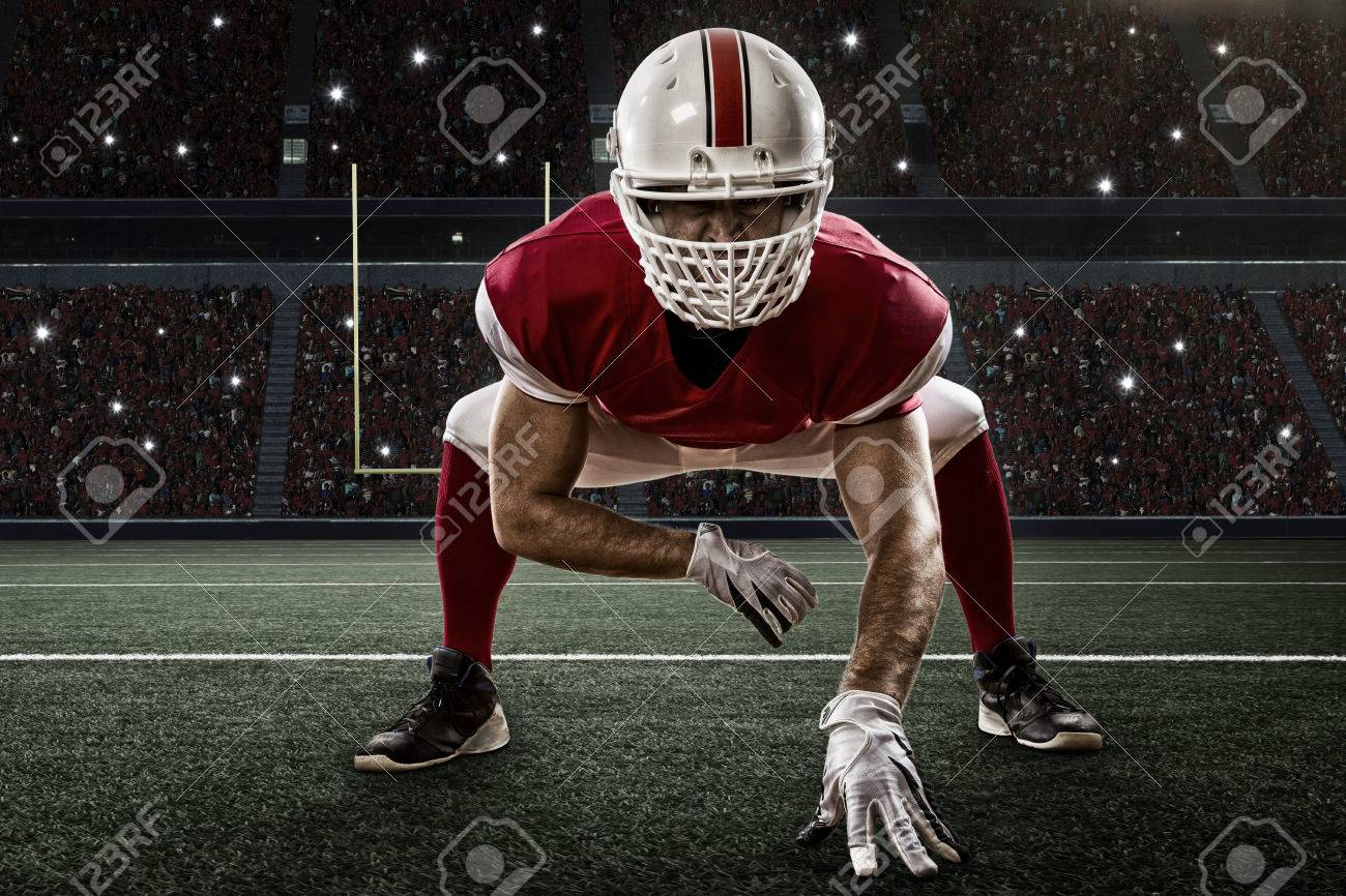 Football Player with a red uniform on the scrimmage line, on a Stadium. - 35219303