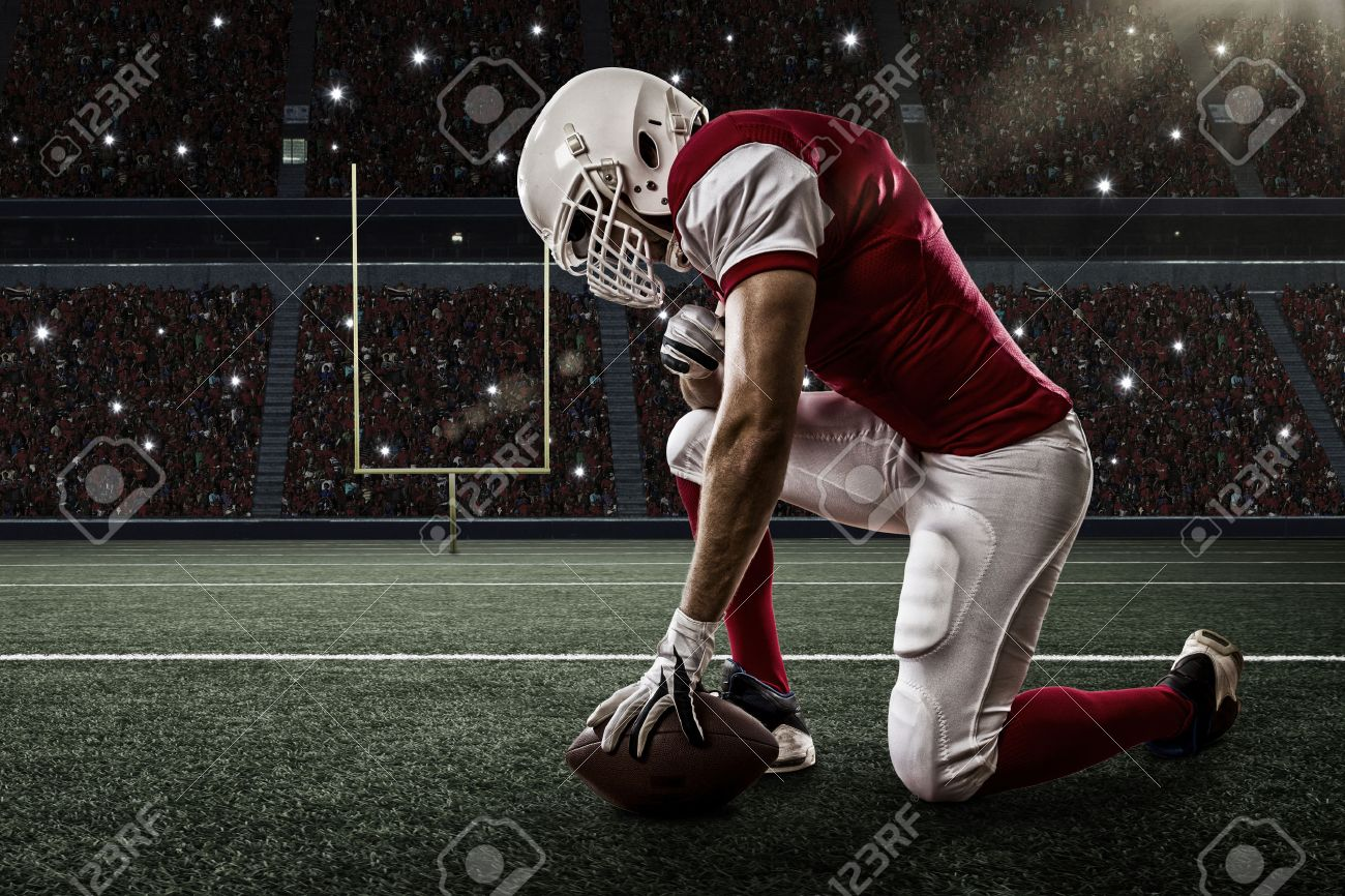 Football Player with a red uniform on his knees, on a Stadium. - 35219385