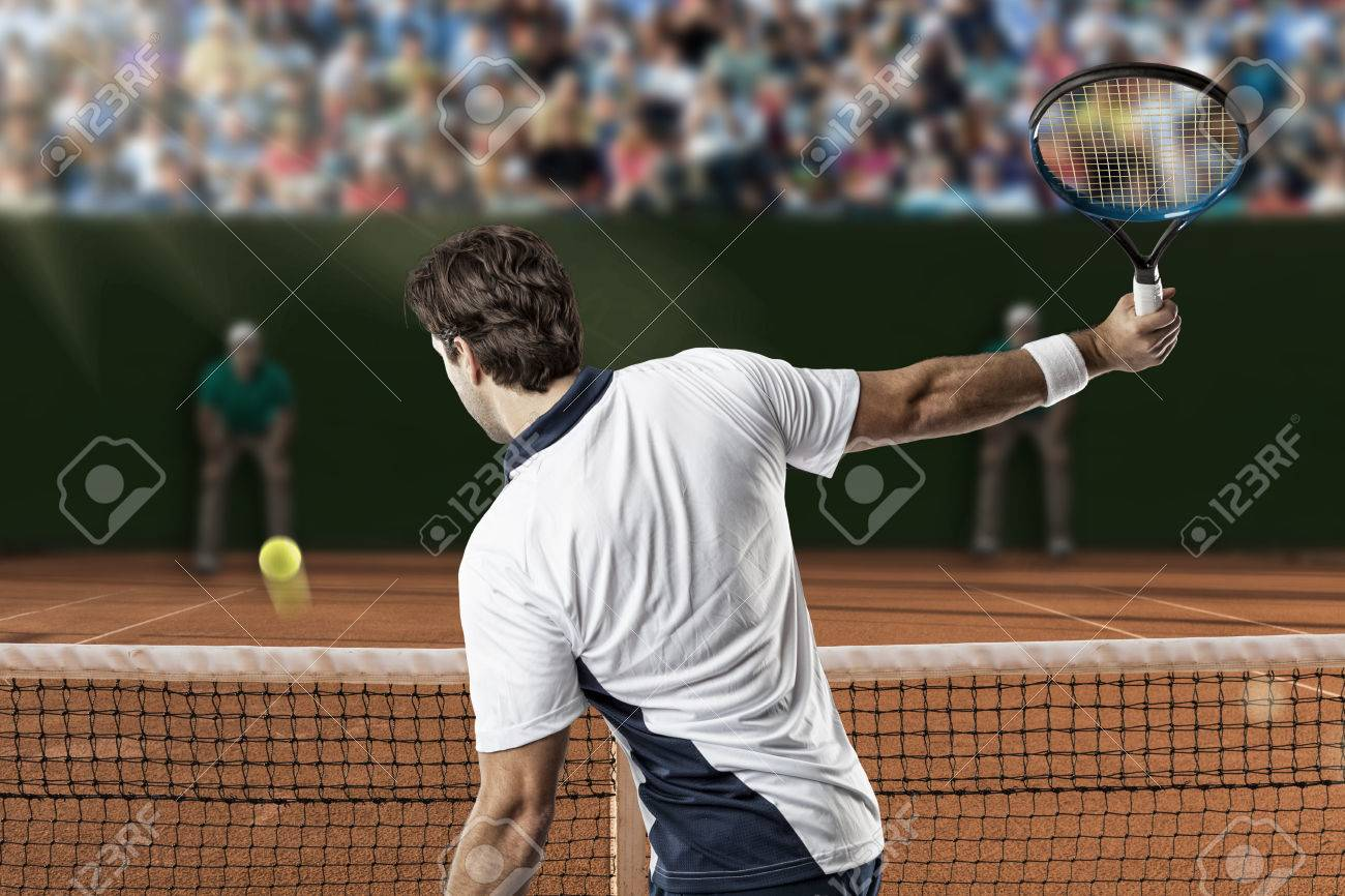 Tennis player returning a ball on a clay tennis court. - 40391808