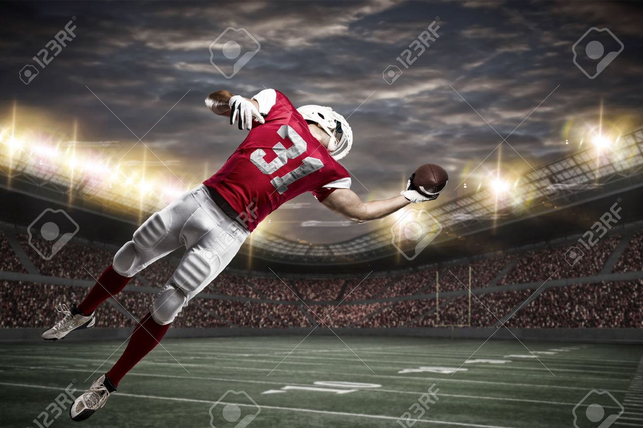 Football Player with a red uniform catching a ball on a stadium. - 50884852
