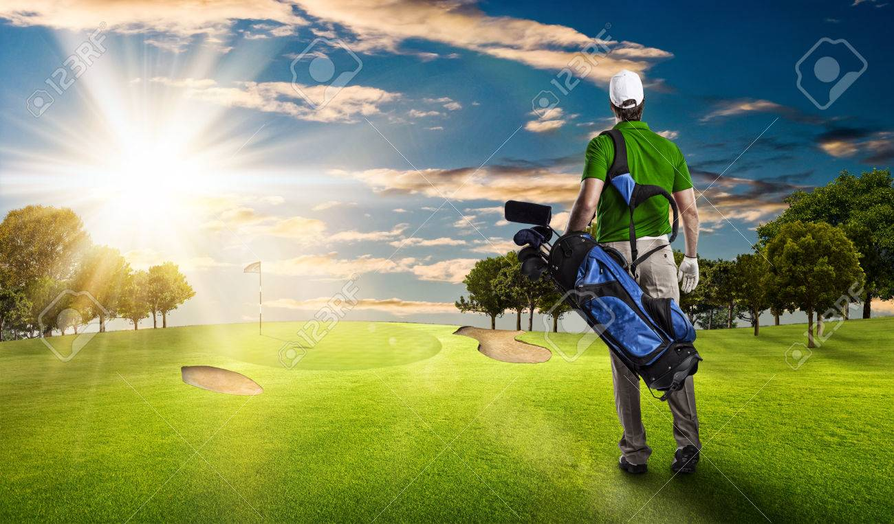Golf Player in a green shirt walking with a bag of golf clubs on his back, on a golf course. - 53264250