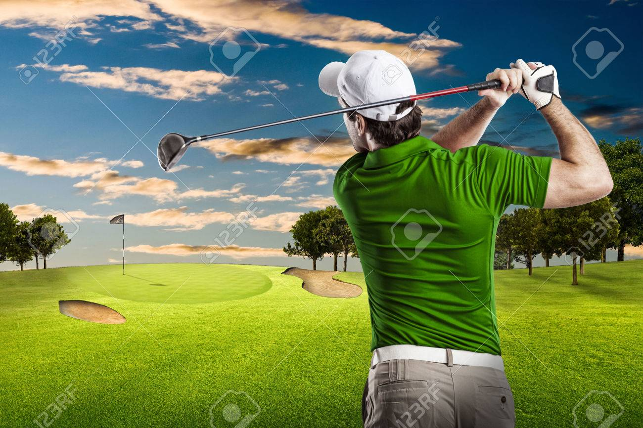 Golf Player in a green shirt taking a swing, on a golf course. - 53264410