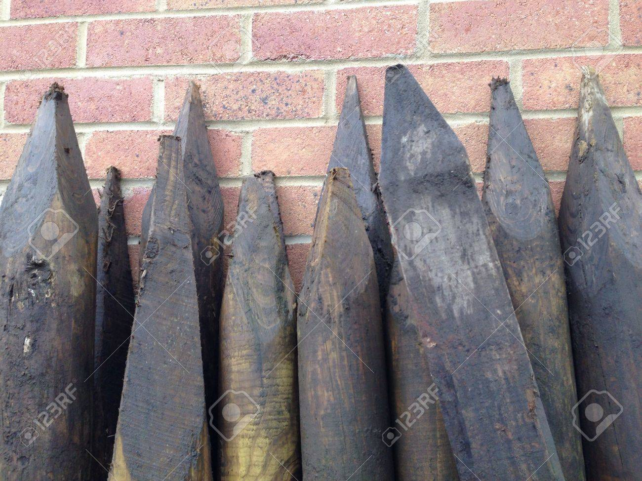 the sharpened pointed ends of wooden fence posts leaning against a brick wall stock photo
