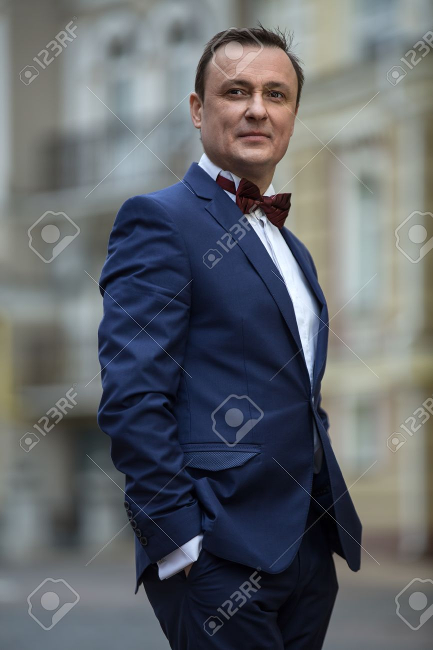 Stylish Man In A Blue Suit With A Butterfly Tie On The Street ...