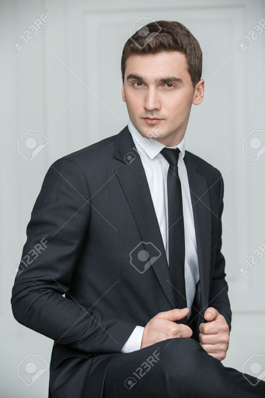 Solid Young Man In Black Suit And Tie. Studio Portrait Photography ...