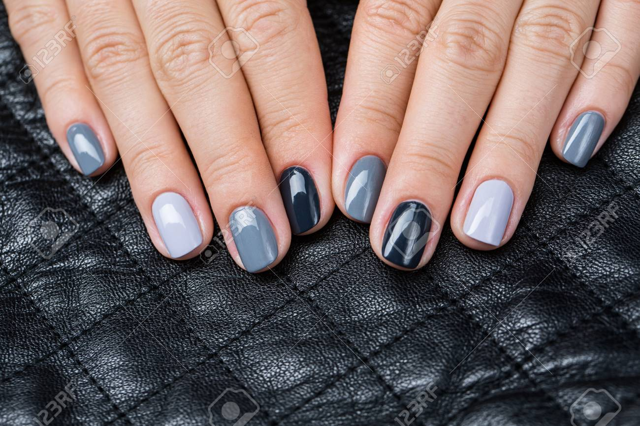 Stock Photo - Women s hands with a stylish manicure. On each nail lacquer  struck with a different shade of gray. Background in the form of small  squares ... 84510ee05